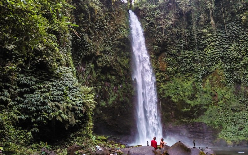 Couple standing at the foot of the Nungnung waterfall in Ubud, Bali