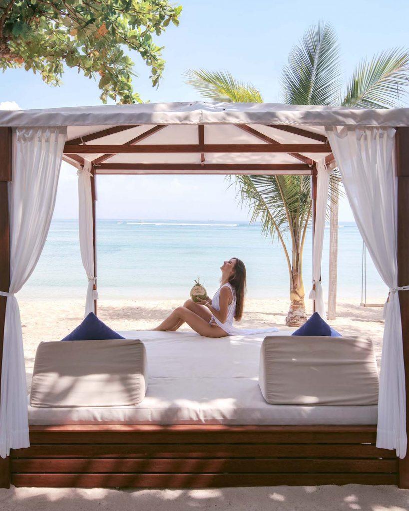 Lady enjoying Melia Bali's beach cabana