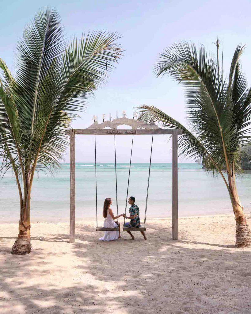 Couple on swing on beach Melia Bali