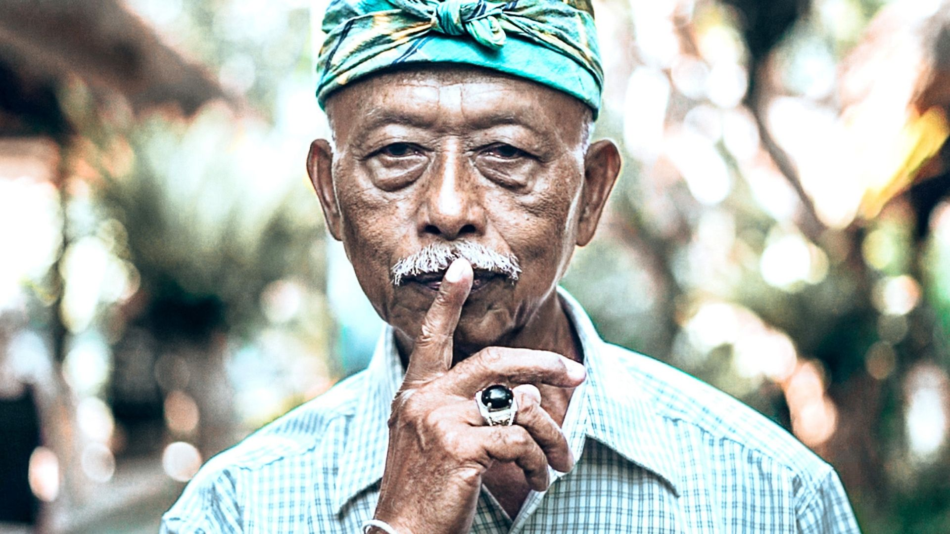 Old Balinese man with index finger on his lip to indicate silence on Nyepi Day