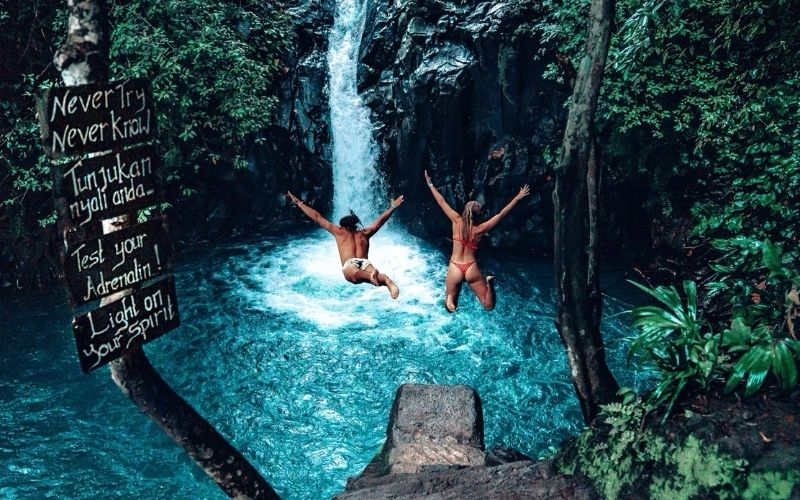 Couple Jumping in The Aling Aling Waterfall in Bali
