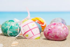 Colorful Easter eggs on a tropical beach