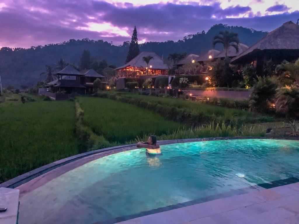 Woman enjoying a Bali sunset from the pool of Samanvaya Resort in Sidemen