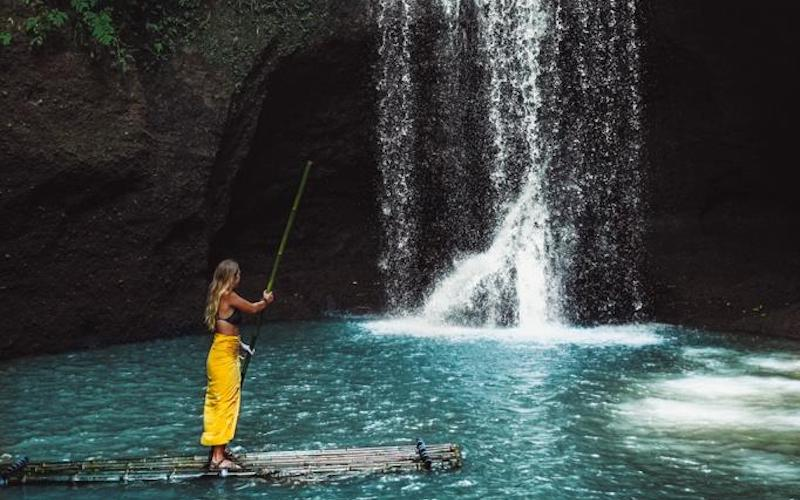 Girl on a stand-up paddle board at the foot of the Suwat Waterfall in Bali