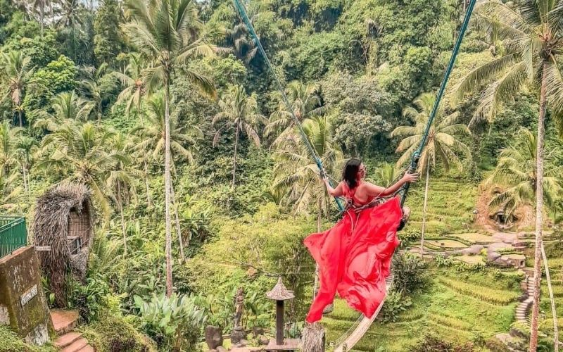 Woman in red dress on a swing in the rice paddies in Bali